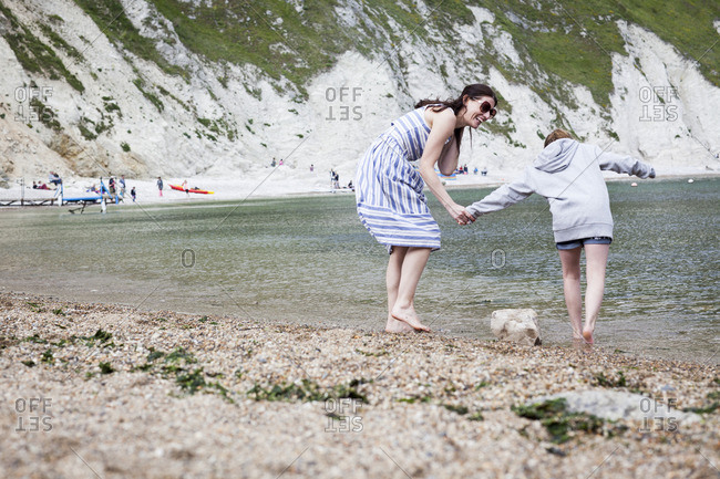 Woman with daughter wading into water at beach