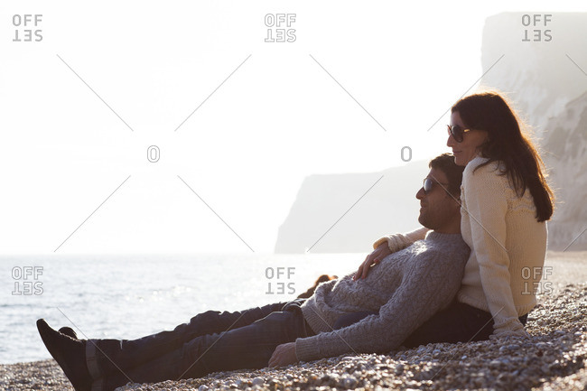 Man leans against his partner on beach at sunset