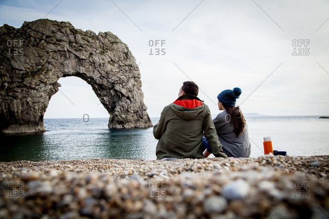Man and woman gazing at Great Pollet Arch from beach in Ireland