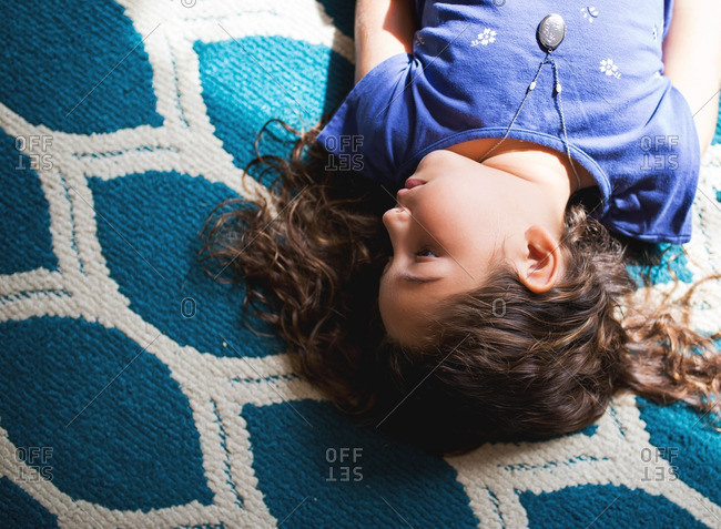 Girl lying on blue and white pattern rug
