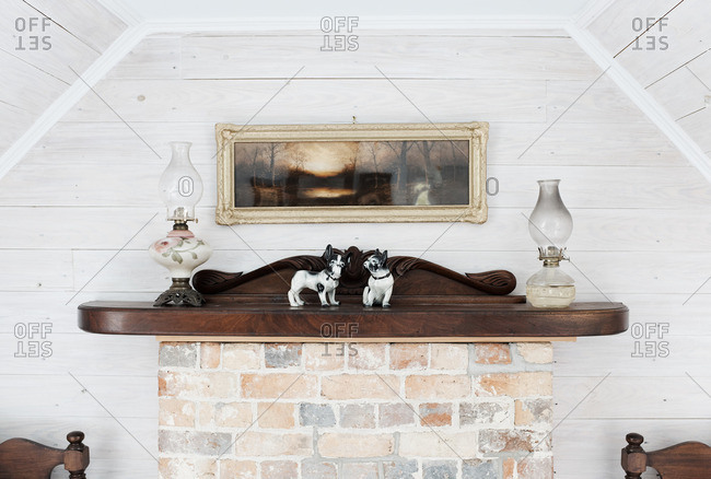 May 2, 2016: Fireplace mantel with porcelain bulldogs and oil lamps