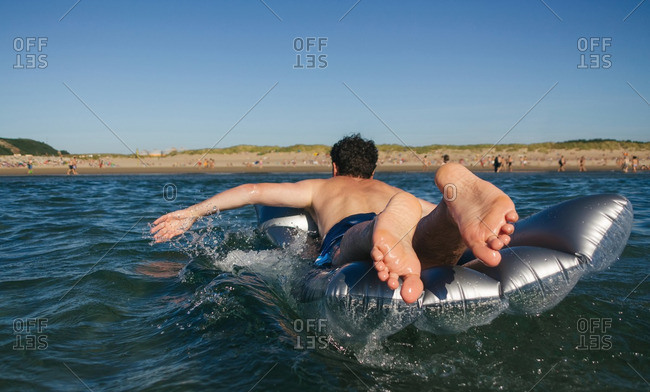 Man lying on airbed swimming in the sea
