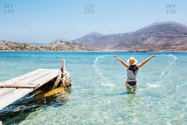 Greece, Cyclades islands, Amorgos, Woman splashing in the blue waters of the Aegean Sea next to a wooden jetty