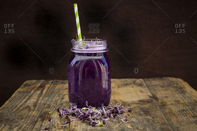 Glass of red cabbage smoothie with beetroot sprouts