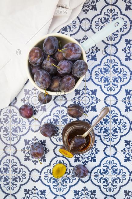 Saucepan of plums and preserving jar of plum jam on tiles