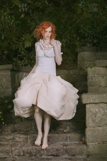 Redheaded young woman in fancy dress walking barefeet on stairs