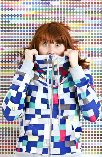 Frightened young woman wearing patterned jacket in front of dotted wall
