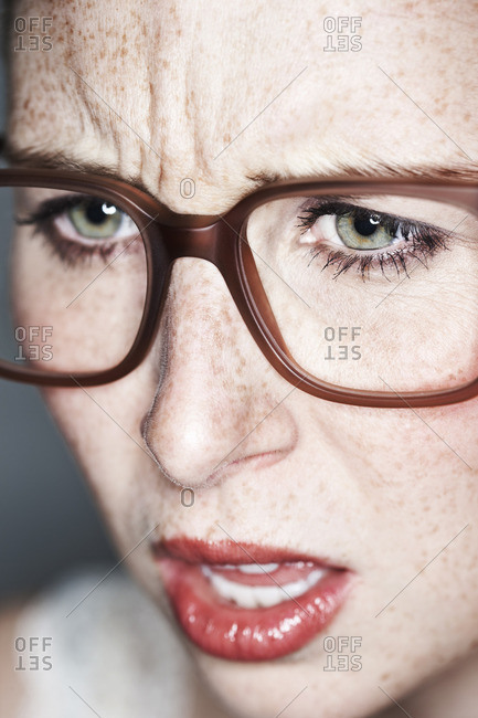 Close up of angry female face with freckles and glasses