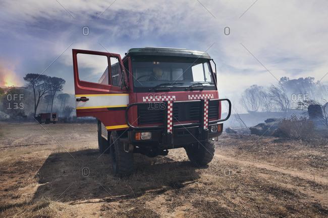 South Africa, Stellenbosch, fire truck parked on devastated land after a bush fire