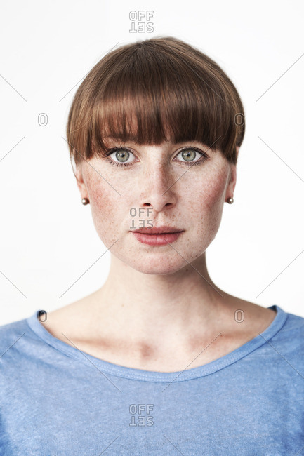 Biometric passport photo of a green,eyed read,haired woman with freckles and bangs