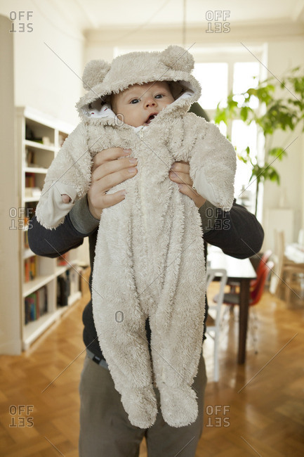 Baby in bear costume being held up by his father