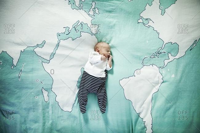 Newborn baby sleeping on blanket with world map