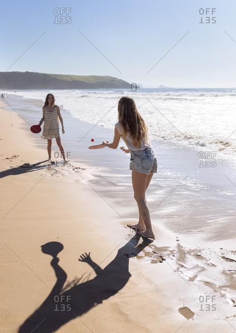Two women playing beach paddles on the beach
