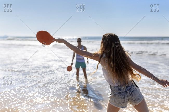 Back view of teenage girl playing beach paddles on the beach