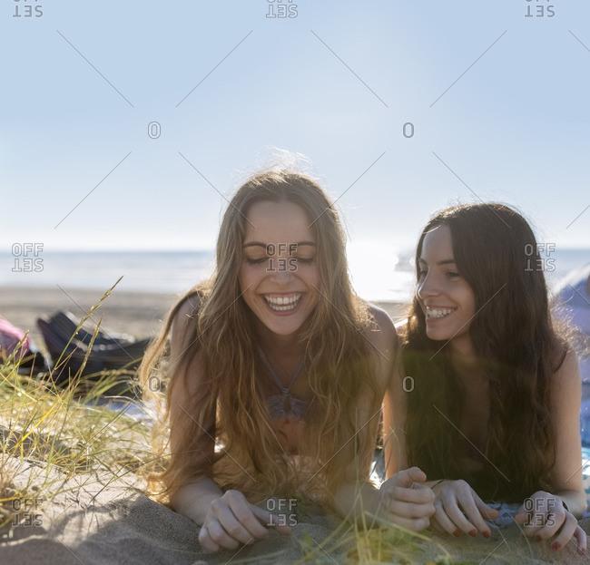 Two best friends lying side by side on the beach