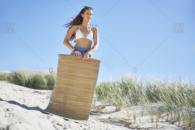 Young woman with beach mat on the beach