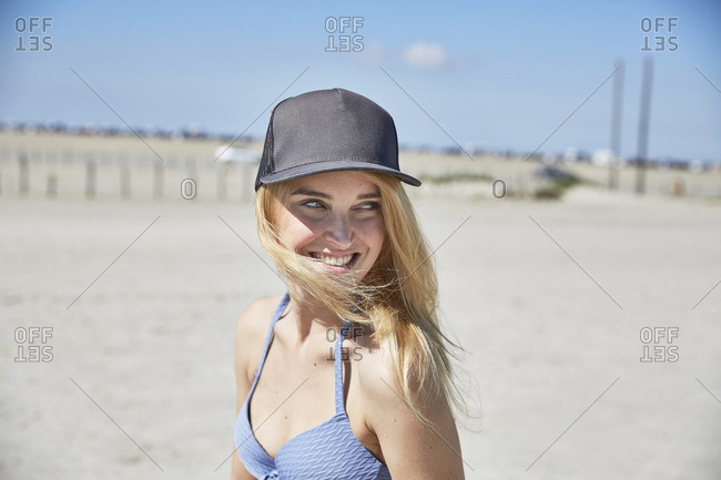 Happy young woman wearing baseball cap on the beach