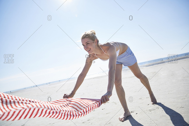 Young woman spreading out towel on the beach