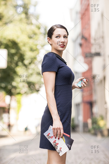 Young woman standing in the city looking around