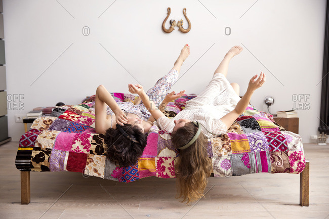 Two best friends lying on bed with legs in the air listening music with headphones