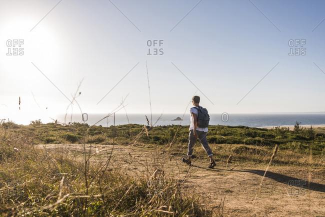 France, Bretagne, Finistere, Crozon peninsula, woman during beach hiking