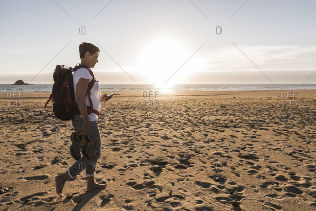 France, Bretagne, Finistere, Crozon peninsula, woman during beach hiking