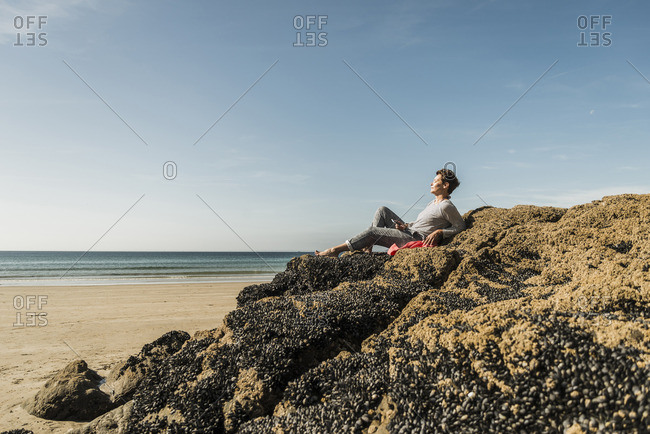 Mature woman relaxing on rock at the beach