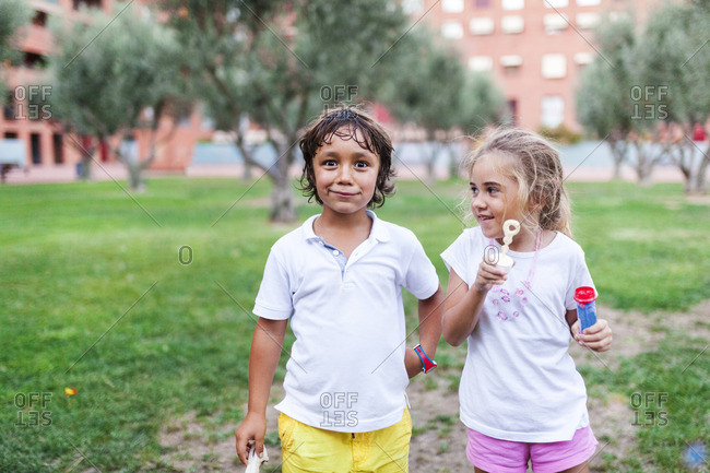 Little girl and boy with bubble rings in a park