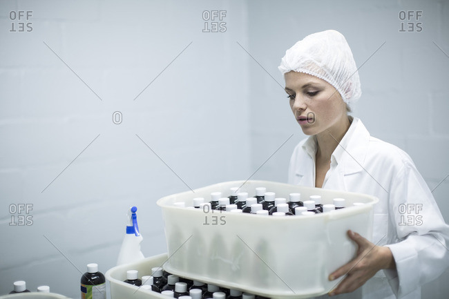 Woman carrying box of medical supplies in medical factory