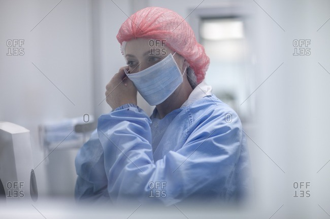 Woman putting on sterile protective clothing