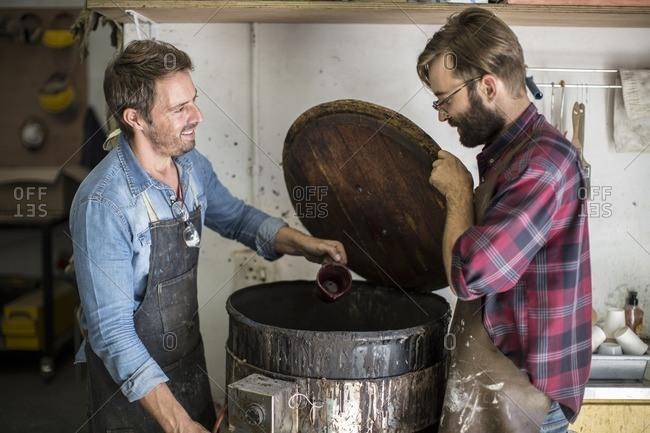 Two men in workshop looking in barrel