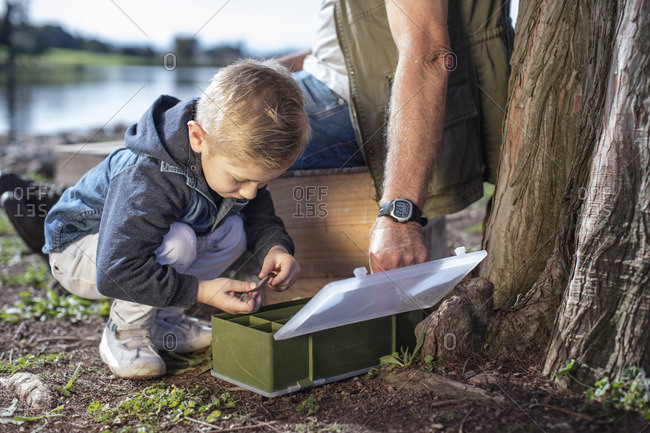 Boy with grandfather taking bait from box