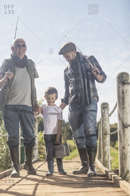 Grandfather, father and son walking over bridge with fishing equipment