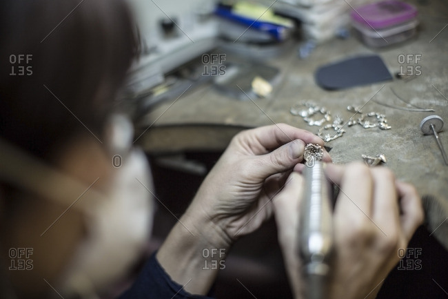 Goldsmith working on jewelery in workshop