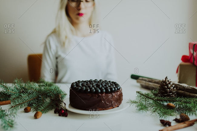 Woman sitting in front of a chocolate cake at a table decorated for the Christmas holiday