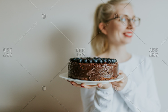 Portrait of a woman holding a chocolate cake topped with berries