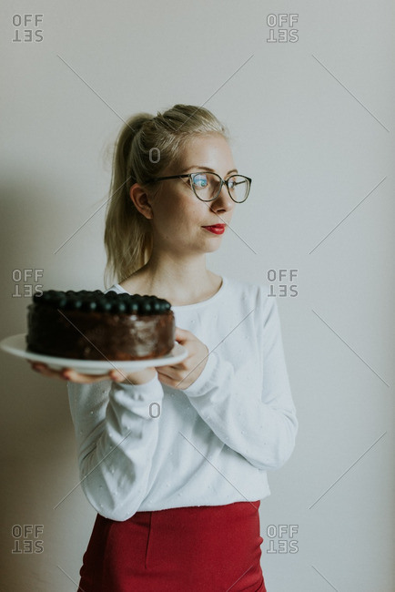 Fashionable young woman holding a chocolate cake topped with berries