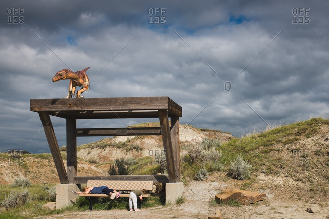 Two children lying down on a bench at the Dinosaur Provincial Park in Alberta, Canada