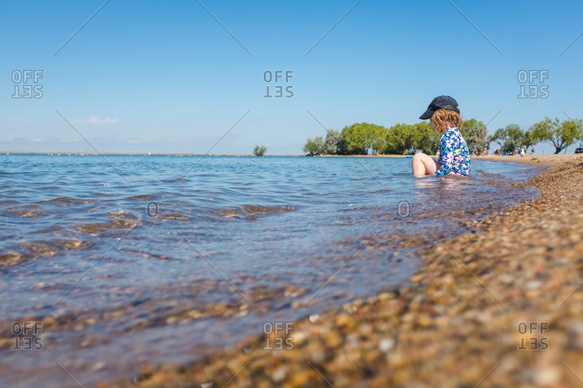 Child sitting down in the water along a rocky shoreline