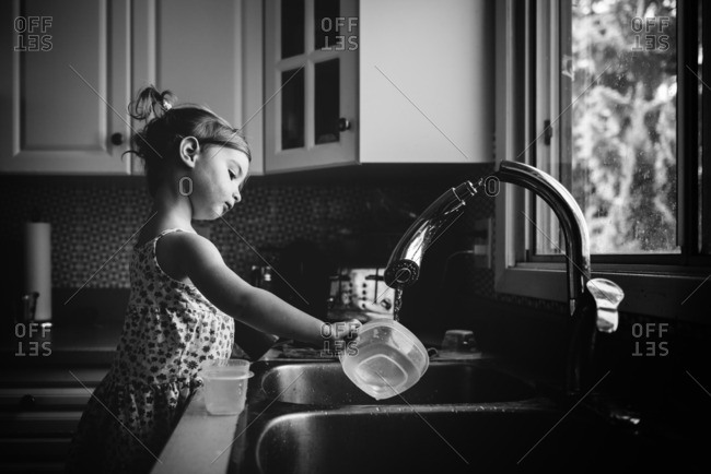 Girl rinsing a dish in the sink