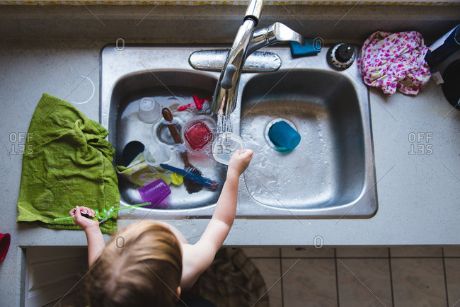 Toddler rinsing a dish in the kitchen sink