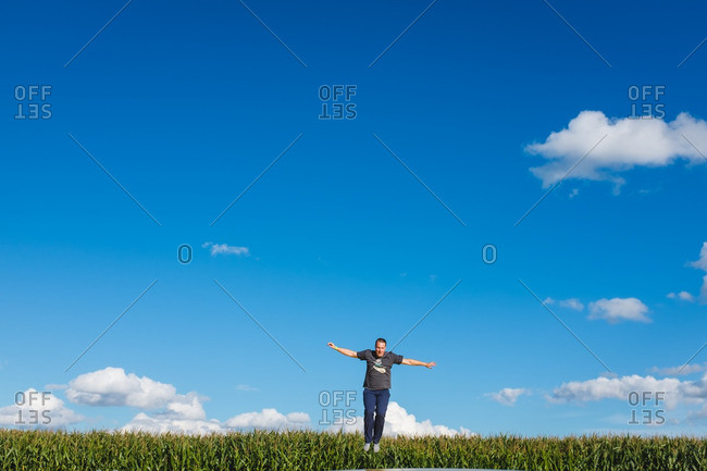 Man jumping on a trampoline near a cornfield