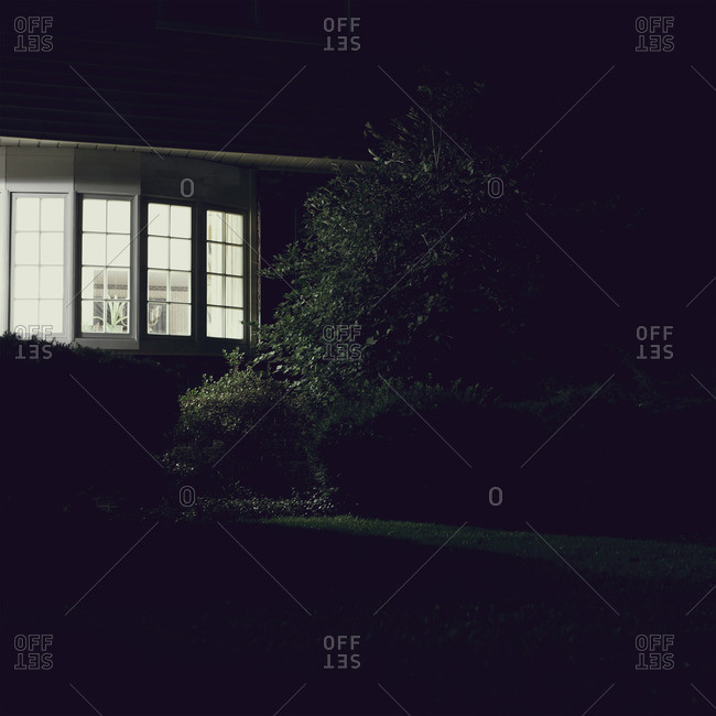 Suburban home with light on at night