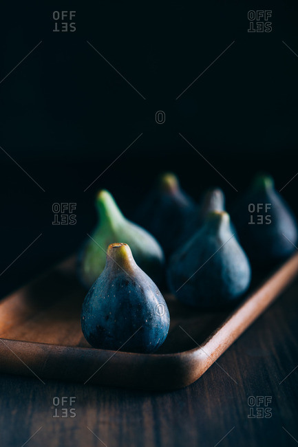 Figs on a wooden tray over a dark background