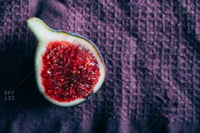 Sliced fresh fig on a purple cloth