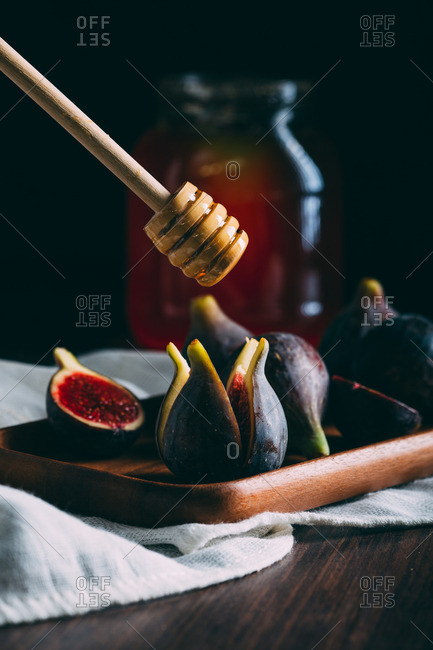 Sliced fresh figs on a wooden tray over a white cloth with honeycomb