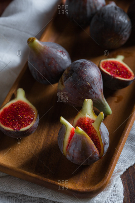 Figs on a wooden tray over a white cloth