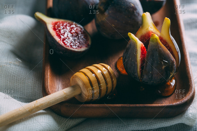 Fresh figs on a wood tray over a white cloth with honeycomb
