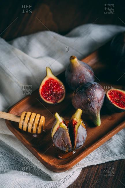 Sliced fresh figs on a wood tray over a white cloth with honeycomb