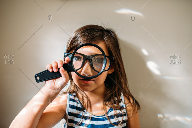 Girl in eyeglasses holds a magnifying glass in front of her face